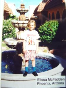 Elissa McFadden on a fountain in Phoenix wearing her Young's Dairy t-shirt