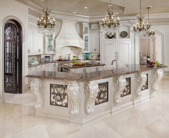 White on white can be elegant on its own but add the white cabinets and white marble style floors here and you're over the top. With the bronze colored countertops and plenty of chandeliers, not to mention the elegant gateway, you've got one of the best designer kitchens here.
