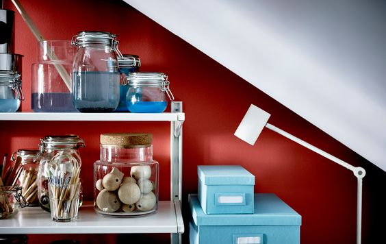 A shelving unit is stocked with crafting supplies and sits beneath a sloped ceiling.