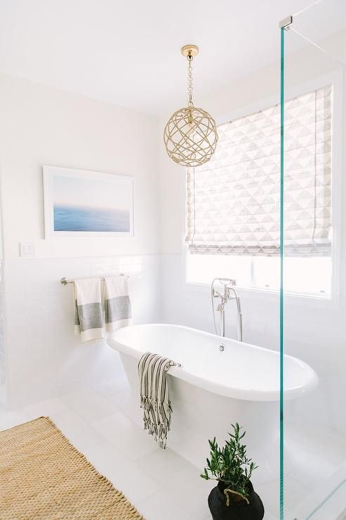 A Rope Pendant Light Hangs Over A Roll Top Freestanding Bathtub