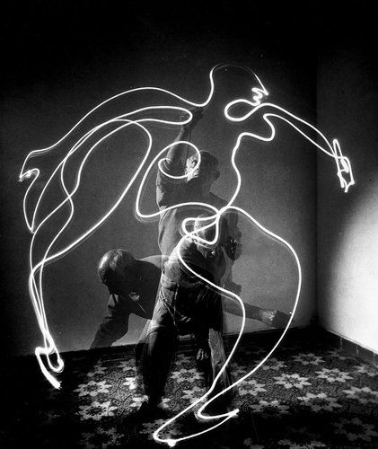 """Remarkable Photos Show Picasso """"Painting"""" With Light - A running figure, with Picasso in motion behind it."""