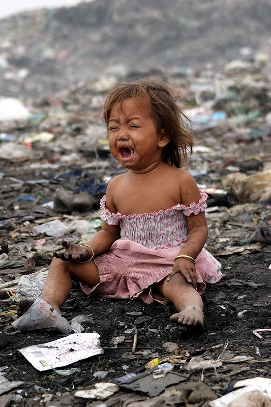 At Stung Meanchey A young girl cries while sitting in ...