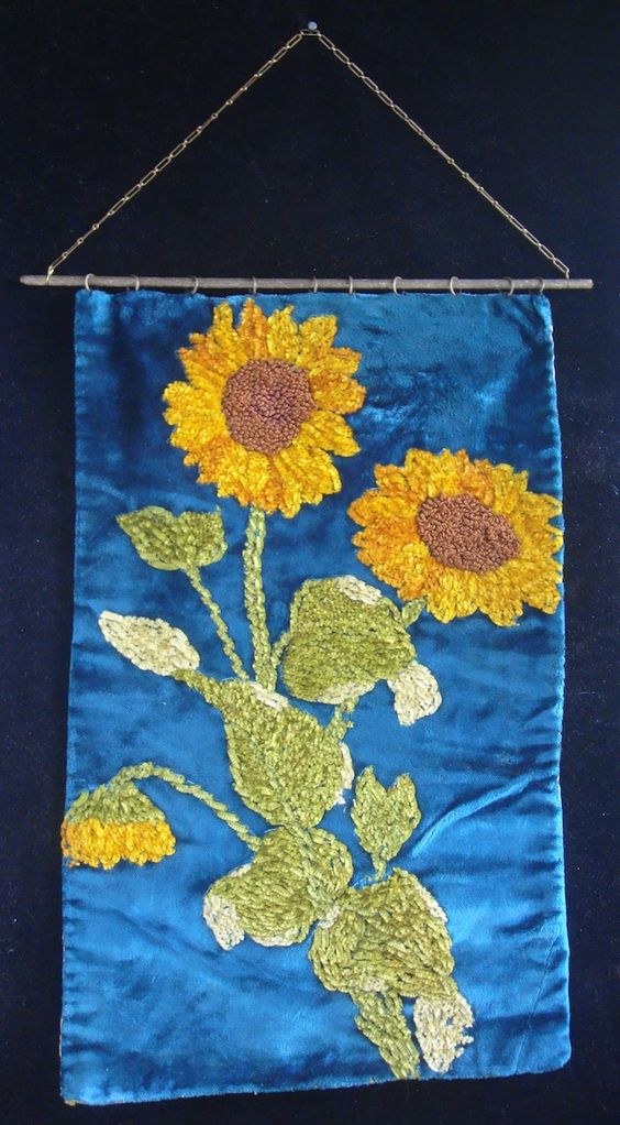 Victorian tabletop heat screen. Placed between the fireplace and a person to shield their face from heat. Chenille embroidered sunflowers on velvet. The sunflower, calla and peacock feather were the three symbols of the Aesthetic Movement.