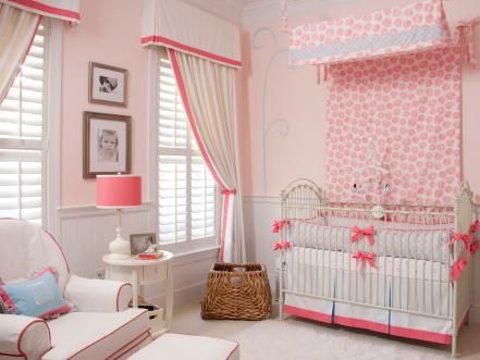 To add drama and height to the room, designer Liz Carroll of Liz Carroll Interiors creates a floral-printed canopy over the iron crib. So that the room isn't overwhelmed in pink, she uses white fabrics on the curtains and chair and trims them with hot pink.