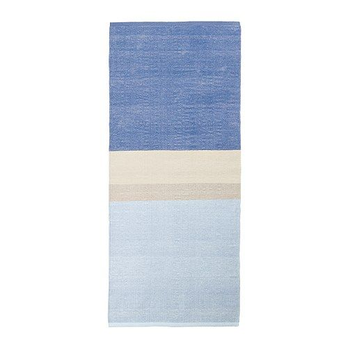 Low pile, reversible rug from Ikea stores.  Medium blue, ivory, tan, and light blue color block pattern.  We have had good luck using duct tape on the back of smaller rugs to make a larger rug.