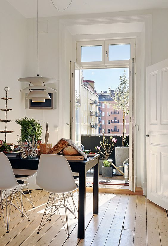 Charming Midcentury Modern interior design in a Paris apartment with the French doors wide open to the city!