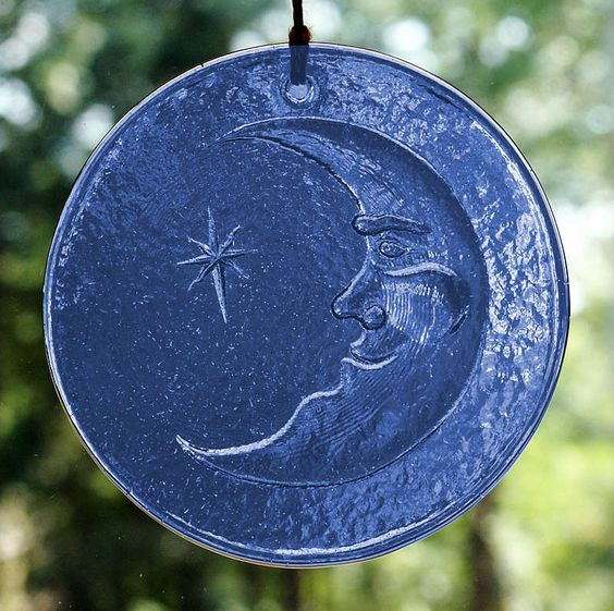 """Moonbeams Suncatcher - Grinning Man in the Moon peers at a single star. Made of cobalt glass. Approx. 4"""" in diameter. Comes with a hemp cord and glass beads for hanging."""