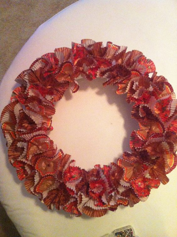 Cupcake holder wreath: styrofoam wreath, sewing pins, and four different fall pattern cupcake holders (about 75) cute and inexpensive decoration!!