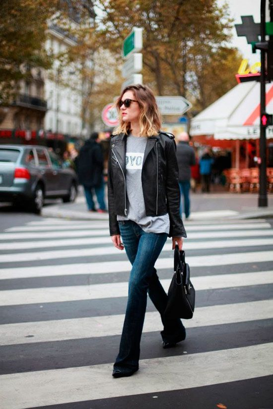 How To Wear Flare Jeans (even if you are petite): Woman wearing a black leather jacket, a grey graphic t-shirt, flare jeans, black heels and a black handbag.