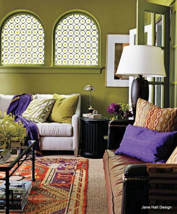 Bohemian style living room with moss green walls and violet purple accents paint color Purple accent wall in living room