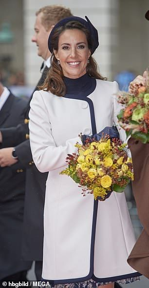 Marie looked in high spirits as she was presented with a bouquet of flowers...