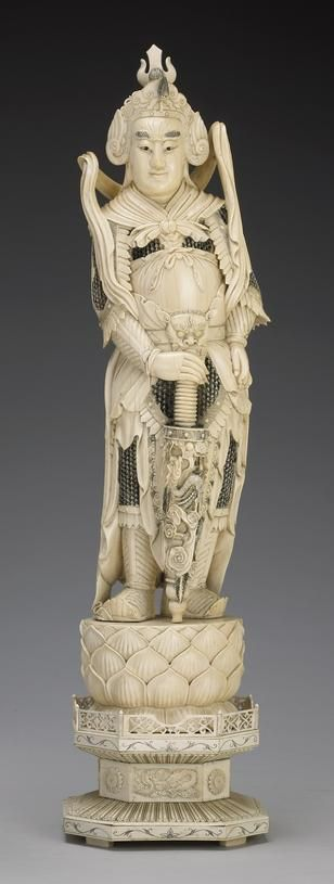 A large pieced ivory figure of Weituo The Buddhist guardian general identified by his young face, warrior's armor and vajra shaped sword as as he stands upon a lotus blossom attached to a waisted base overlaid with ivory tiles, the surfaces highlighted with black pigment (age cracks, tiny chips). Height 30 1/2in (77.5cm)