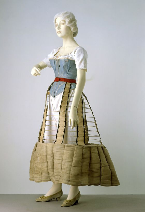 1860 Crinoline frame made from hoops of spring steel covered in braid. The hoops are fixed to black edged tapes wth stamped metal eyelets. There is a red woollen waistband with a frill made from horsehair, and an elastic stay holds the hoops in place.