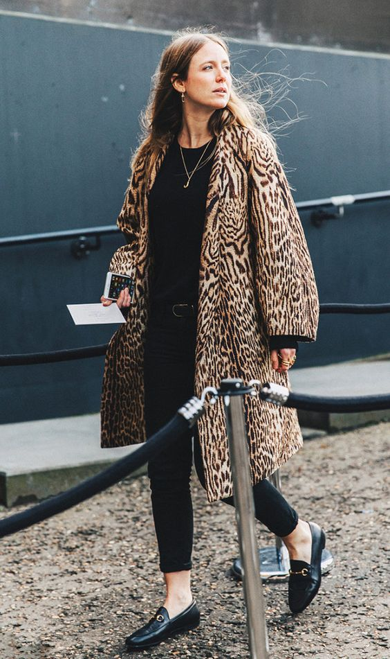 Contrast an all-black look with a printed winter coat.: