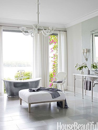 Designer Marshall Watson turned this master bath into a spa-like oasis with floor-to-ceiling windows, a Waterworks cast-iron tub, a custom vanity with crystal bars, also by Waterworks, and a crystal chandelier from John Salibello. Walls are Silver Satin in Aura by Benjamin Moore.