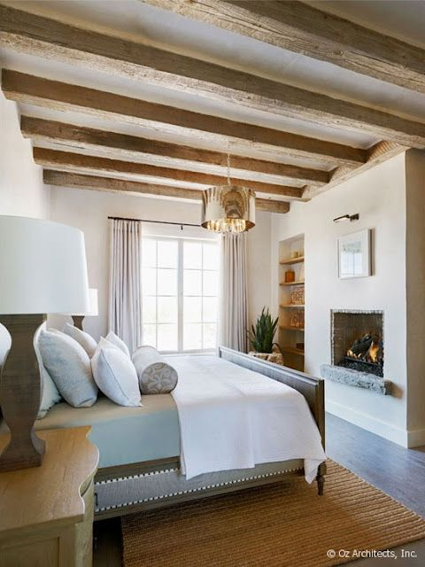 a great bedroom with a fireplace and beams