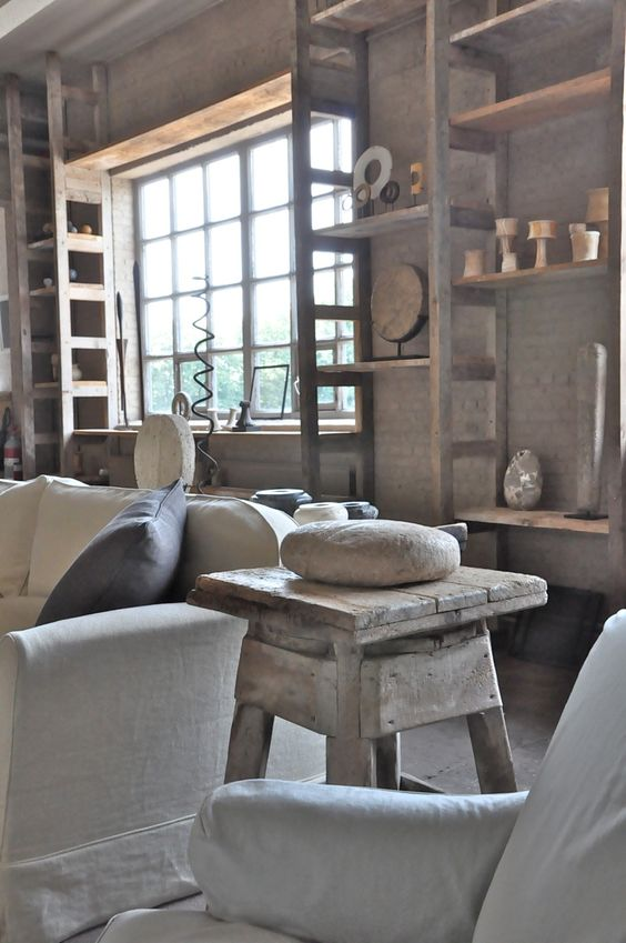 Pale earthy colors in lofty warehouse space by #AxelVervoordt with rustic wood, #Belgianlinen, and modern art