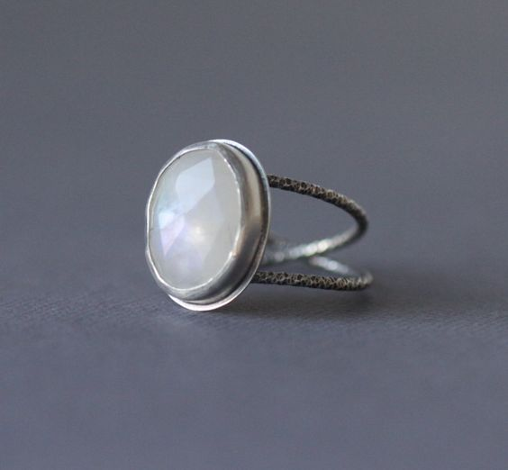 A rose cut moonstone sparkles in a sterling bezel set on a continuous looping band, we call an infinity band, since it has no end or beginning, symbolizing the everlasting. All reclaimed sterling silver. All handmade. Size 7.5