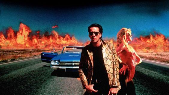 """Vor 25 Jahren startete 'Wild At Heart' von David Lynch im Kino.-Die Kinohistorie kennt unzählige Beispiele von heißblütigen Liebschaften, die scharf am Rande des Wahnsinns entlangschrammen – von """"Im Reich der Sinne"""" bis zu """"Betty Blue"""". Doch Lynch fährt ein dermaßen absurdes Kitschpanorama auf, dass es einen zuweilen schaudert. Da fliegen sprichwörtlich die Funken, da wird der Sex zur wilden Feuersbrunst – und schließlich gibt Sailor alias Nicolas Cage auch noch den schmalzigsten Elvis aller…"""