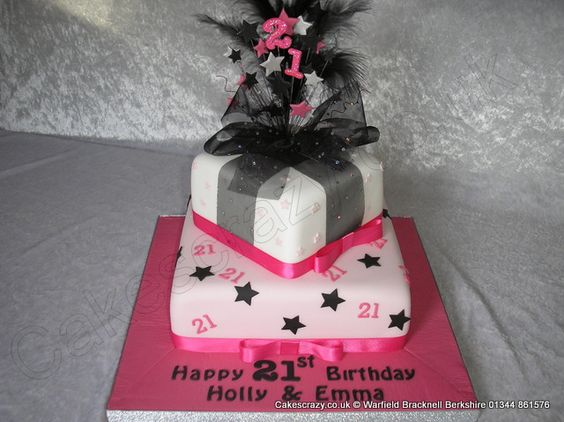 Pink and white iced two tier parcel cake decorated with sugar 21 and stars. Topped with a pink black and silver star wire topper with black feathers and hot pink glitter 21. Finished with black glitter ribbon and bow
