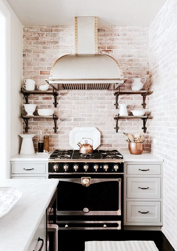 Black and white is classic. It's a simple yet bold statement that can be really be used in any room. In this kitchen, I think the stark white cabinets is offset perfectly by the black oven.  The amazing distressed white brick backsplash continues the feeling of old world charm. I love the open shelves one either side of the stove. If I were to change up one things, I would rather have wide oak floors rather than black tile on the floor to echo the wooden shelves on either side of the oven.
