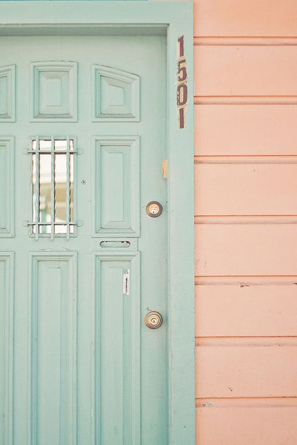 Peachy pink horizontal siding on a coastal cottage house exterior with a seafoam minty green painted door. Come see the Best Sophisticated, Chic and Subtle Pink Paint Colors!