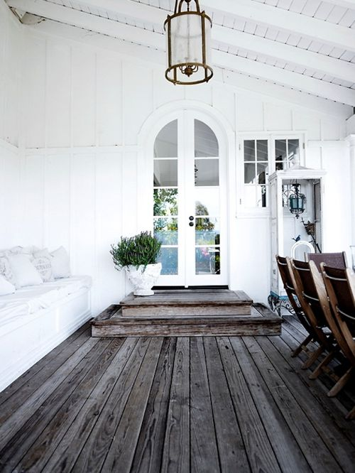 inviting porch - door, cushioned seating over storage, weathered floor, white ceiling