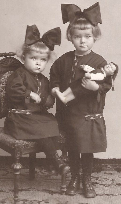 two sisters, one holding doll: