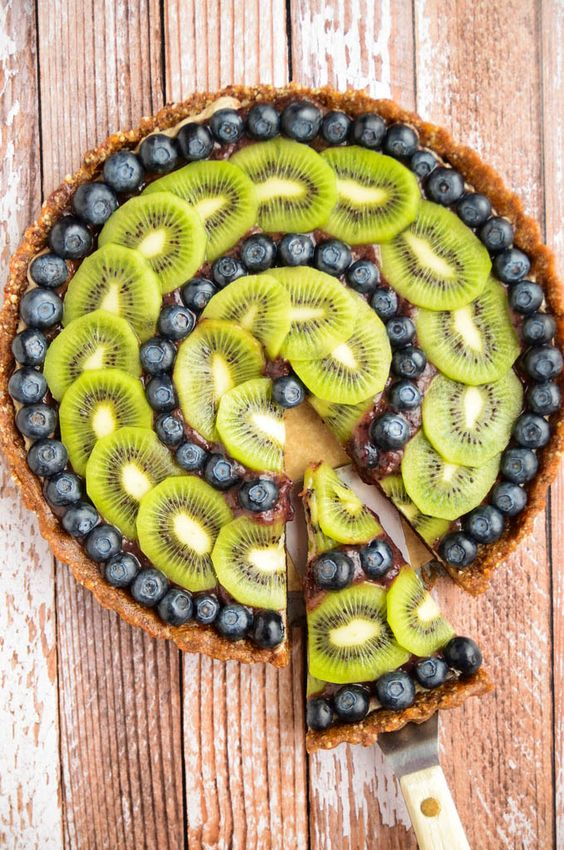 Raw Blueberry and Kiwi Tart (Vegan) Raw crust made with almonds, dates, vanilla bean, cinnamon, and nutmeg, topped with a banana-cashew cream, layered with a kiwi-blueberry glaze, then finished with a symmetrical arrangement of kiwis and blueberries #fruit