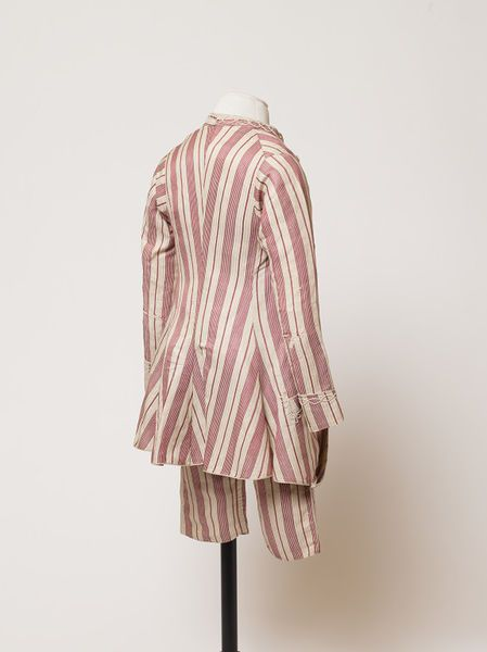 Back view, boy's suit, England c. 1760 (made). Cream coloured silk and cotton blend, patterned with cherry red stripes.