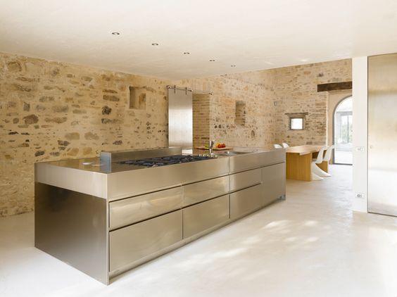 """Die spiegelnden Chromstahl-Flächen der Kochinsel, der Küchenfronten und der Schiebetür zu Wirtschaftsraum und WC bilden einen starken Kontrast zum alten Gemäuer und reflektieren dessen warmtonige Farbigkeit. (Küche: <A HREF=""""http://www.arclinea.it"""" TARGET=""""_blank"""">Arclinea</A>)"""