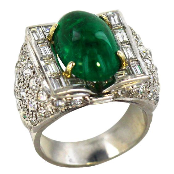 This unusual platinum Art Deco ring features a large cabochon emerald and old mine-cut diamonds. The deeply saturated bright green center stone is flanked on two sides by sparkling baguettes; densely packed round diamonds cascade onto the ring shank.