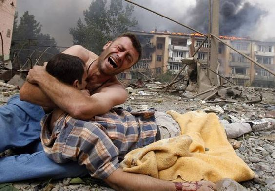 """""""A Georgian man cries as he holds the body of his relative after a bombardment in Gori, 9 August, 2008. A Russian warplane dropped a bomb on an apartment block in Gori, killing at least 5 people. The bomb hit the five-story building close to Georgia's embattled breakaway province of South Ossetia when Russian warplanes carried out a raid against military targets around the town."""""""