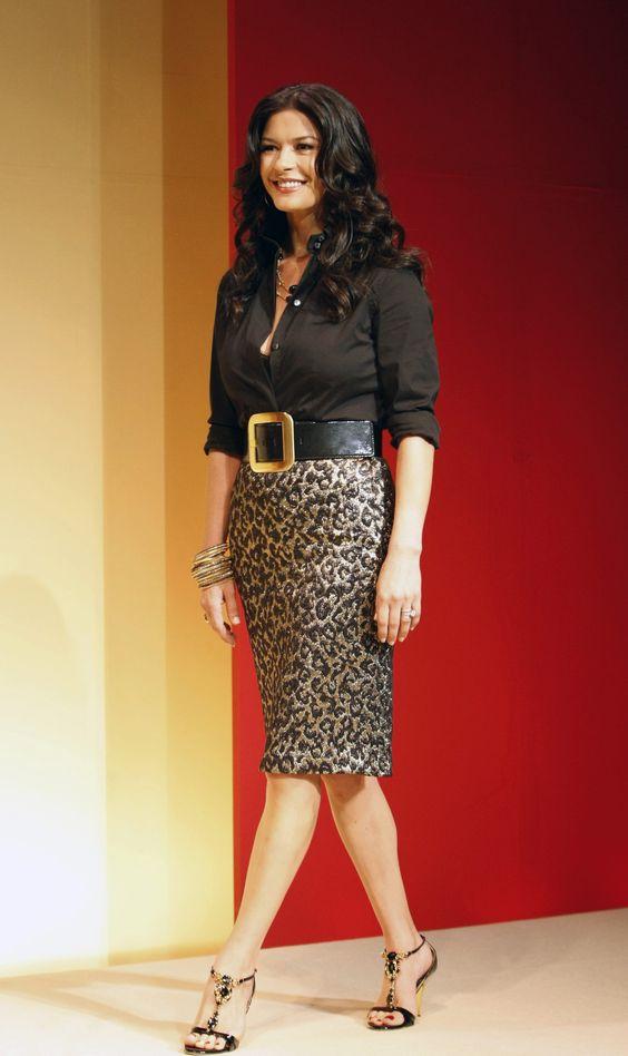 CZJ har mönstrat på nederdelen för att dra fokus dit, markerar midjan med skärpet och har en djupt uppknäppt (= skarpt v-ringad) skjorta i diskret färg för att balansera storbyst+breda axlar med smala höfter.