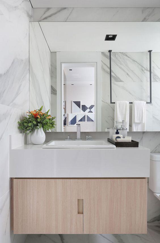 Decoração de apartamento pequeno e integrado. No banheiro, gabinete de madeira, pia branca, cuba branca, vaso branco com plantas. #casadevalentina #decoracao #decor