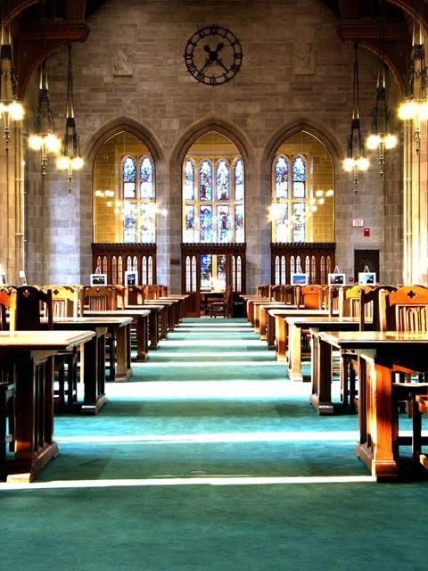 Reading room at Harvard Divinity School library. Stone walls. Arched Stained Glass windows.