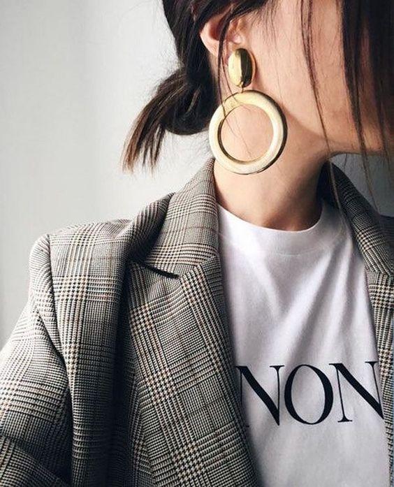 Frau mit Shirt und Blazer trägt große Ohrringe Statement Ohrringe Outfit Inspiration