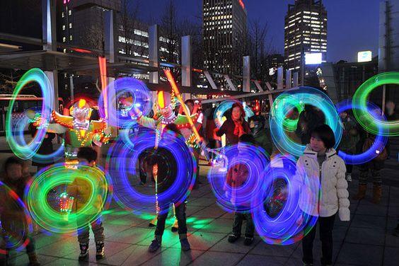 Seoul, Südkorea. Kinder spielen mit bunten blinkenden Lichtstäben. Die Spielzeuge sind Teil einer Lichtshow, die die Südkoreaner auf den ersten Vollmond im Mondkalender einstimmen soll.
