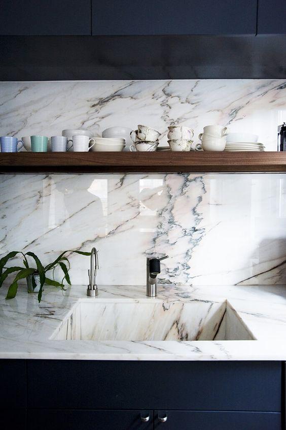 Tout en marbre, l'évier et le plan de travail ne font qu'un. Celui-ci se prolonge sur le mur et fait office de crédence. La blanc veiné du marbre est mis en valeur avec le contraste des meubles de cuisine, d'un bleu profond, presque encre. Malgré la froideur des couleurs et des matériaux, l'ensemble est réchauffé par l'étagère en bois et les éléments de vaisselle posés dessus. #marbre #cuisine #crédence