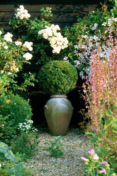 private garden, Sussex. Boxwood topiary sphere in pot at end of path as focal point