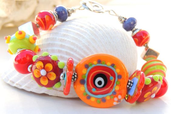 This pretty bracelet is so fun. I used all handmade artisan lampwork beads and sterling silver components. The focal bead was made by Jasmine French in Germany. The coordinating beads are all handmade in bright, bold colors that will surely make you want to do a jig or two!  This will fit a 7 wrist, however, sizing up or down is always available. Enjoy