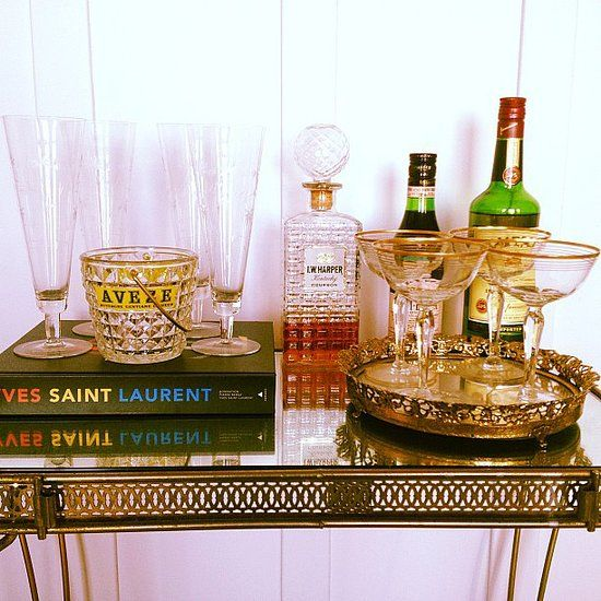 Luxe and Layered Although the main purpose of a bar cart is to display spirits, accessories add luxe and interest. Display glasses on a small tray, and use statement books to add a personal touch. Source: Instagram user ashleybrookesf