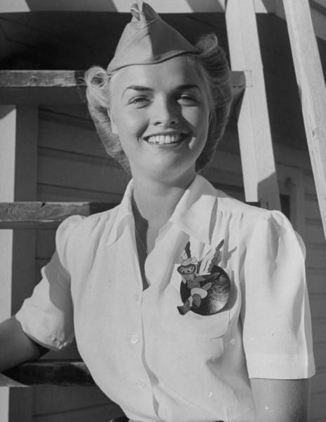 Anne Armstrong McClellan, pilot trainee in Women's Flying Training Detachment, sporting an official dress uniform of white blouse, tan slacks and overseas cap & a Fifinella mascot pin designed for the girl pilots by Walt Disney, at at Avenger Field in Sweetwater, TX, July 1943 (Peter Stackpole).