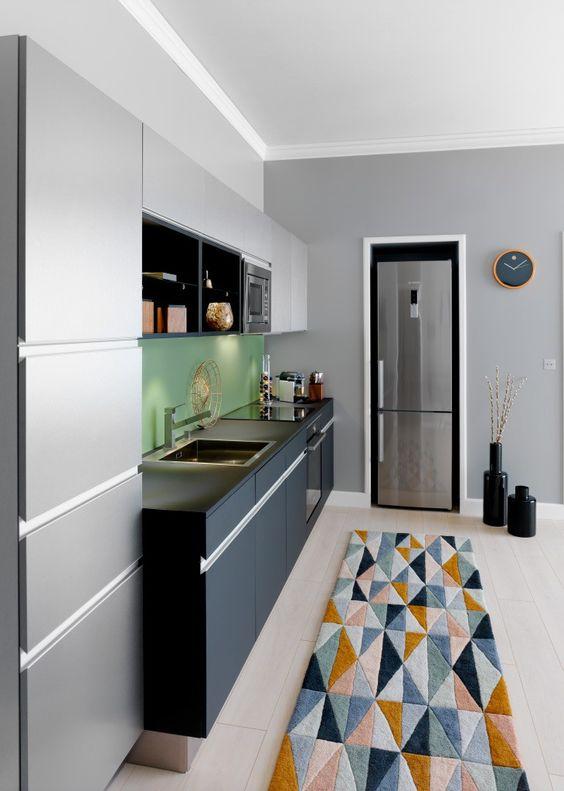 Les différentes nuances de gris de la cuisine Arpège contrastent harmonieusement avec le vert de la crédence et le cuivré des objets déco et du tapis signé BoConcept