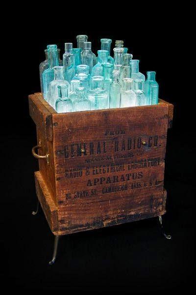Luminária em forma de caixa com garrafas.: