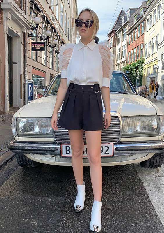 Mangas de organza: a tendência mais fofa da temporada - #GuitaModa. Camisa branca com manga bufante transparente, short preto de alfaiataria, ankle boot branca