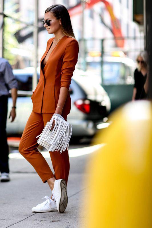 Look con traje sastre tonos tierra, deportivas y bolso de mano blanco