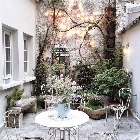Pastels and climbing vines in this lovely European patio. Romantic French Country Garden Courtyard Ideas. #frenchcountry #courtyard #garden #provence #romantic