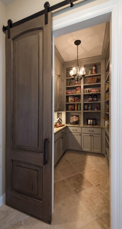 Spacious and organized pantry area with an appealing sliding door that adds character to the entire space.: