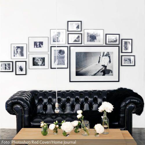Ein schwarzes Chesterfield-Sofa und der moderne Couchtisch aus Holz ergeben einen starken Hell-Dunkel-Kontrast. Die Bilderrahmen in Petersburger Hängung nehmen mit den schwarzen Rahmen die elegant-schlichte Linie der Möbel wieder auf.
